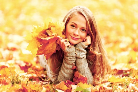 woman in white: woman on leafs in autumn park Stock Photo