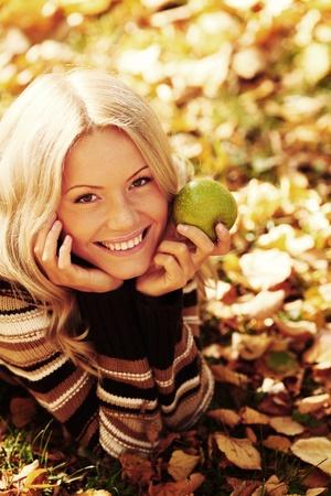 woman eat apple in autumn park Stock Photo - 10916668