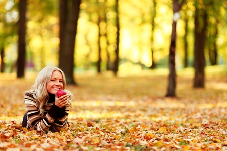 woman eat apple in autumn park Stock Photo - 10917467