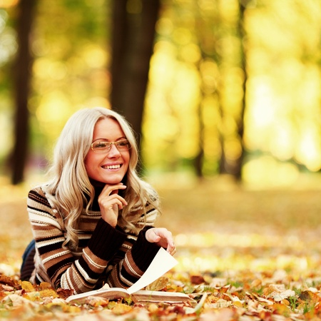 woman read the book in autumn park photo
