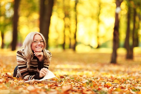 autumn young: woman read the book in autumn park Stock Photo
