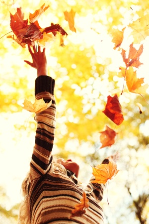 woman in autumn park drop up leaves Stock Photo
