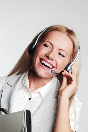 business woman in a headset on a gray background Stock Photo - 10940881