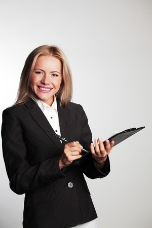 business woman writing in notebook on a gray background photo