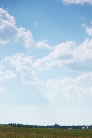 horizon over land:  green field under blue sky