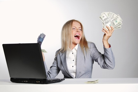 business woman working on laptop dollar in hands photo