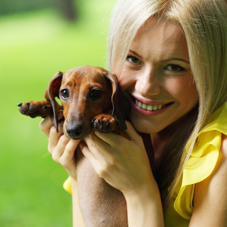 stares: woman dachshund in her arms on grass Stock Photo