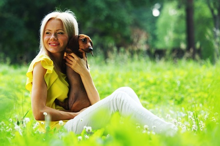 woman dachshund in her arms on grass photo