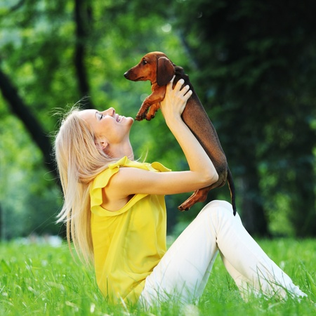 woman dachshund in her arms on grass Stock Photo - 10940539