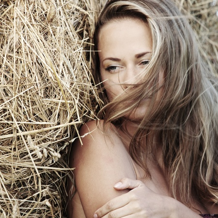 hay: portrait of a girl next to haystack close