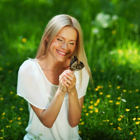 Woman playing with a butterfly on green grass Stock Photo - 10963868