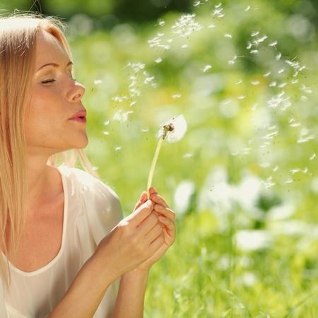 viento soplando: chica con un diente de le�n en su mano tendida en la hierba