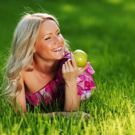 blonde holding an apple in his hand lying on green grass Stock Photo - 10963880