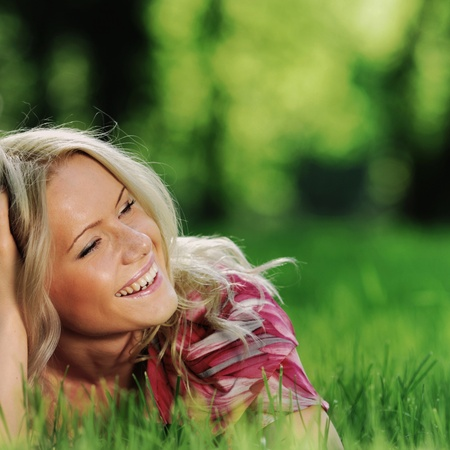 smile blonde lying on green grass photo