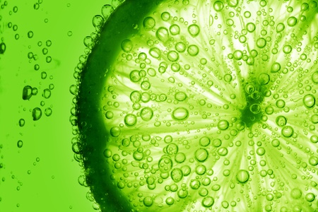 close up: lime slice in water bubbles