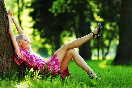 happy girl lying under a tree on a summer day Stock Photo