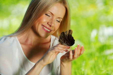 Woman playing with a butterfly on green grass Stock Photo - 10963876