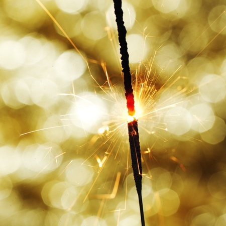 sparkler: sparkler on gold  bokeh background macro close up