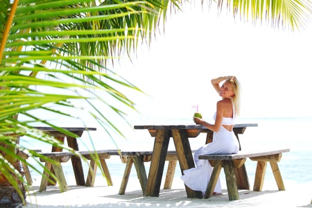 woman sitting in a tropical cafe on the background of a  palm trees and sky and sea Stock Photo - 11031907