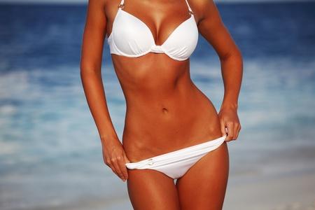 sun tan: woman in bikini on sea background