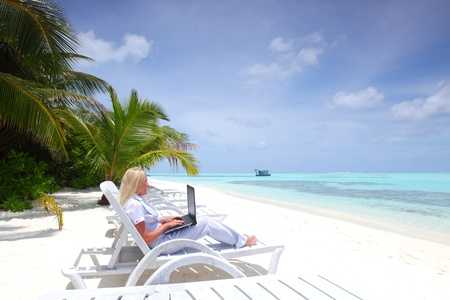 business woman with laptop lying on a chaise lounge in the tropical ocean coast photo