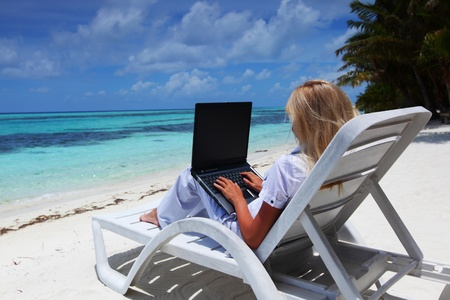 maldives beach: business woman with laptop lying on a chaise lounge in the tropical ocean coast