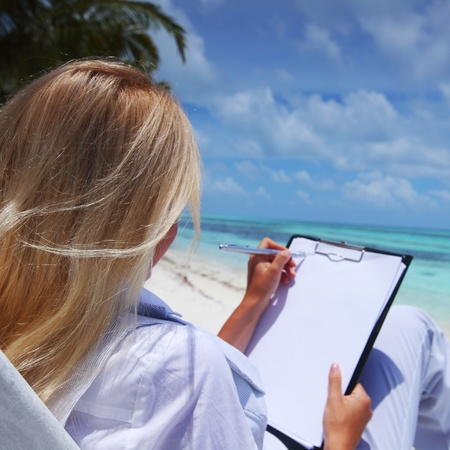 sea sexy: business woman with blank paper lying on a chaise lounge in the tropical ocean coast