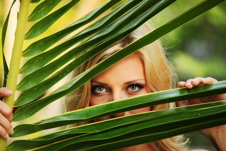 woman hiding behind the palm leaves photo
