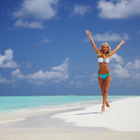 tanned girl: happy girl run along the ocean coast