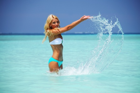 young girl bikini: woman  playing in ocean water