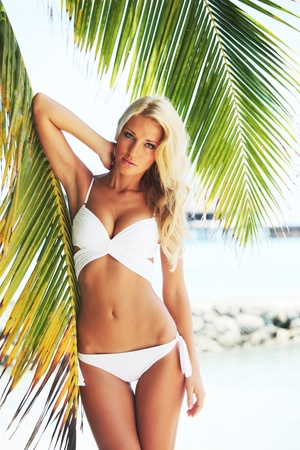 sexual health: woman in bikini under palm on sea background Stock Photo