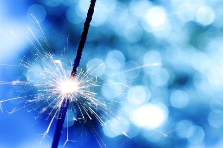 funken: Wunderkerze auf blauem Hintergrund Bokeh Makro Nahaufnahme