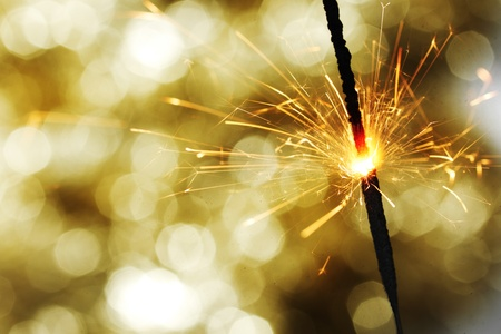 sparkler on gold  bokeh background macro close up