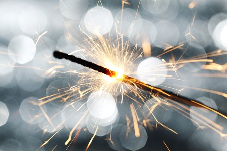 sparkler on silver bokeh background macro close up photo