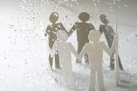 paper team linked together under rain weather concept Stock Photo - 11125479