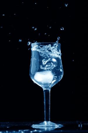 bartend: alcohol splash on black  background