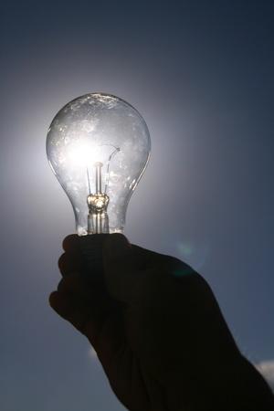 blue light bulb in man finger photo