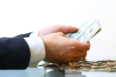 paying money: hands counting dollar money on white background