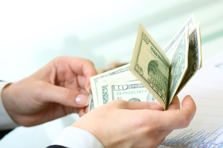 winning stock: hands counting dollar money on white background