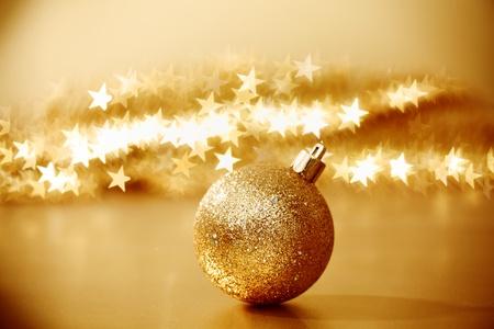 golden christmas ball on golden star bokeh background