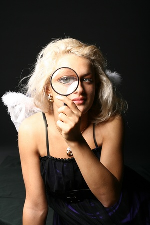beautiful blondie girl with magnifier looka at you