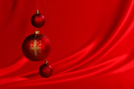 christmas balls on red satin background photo