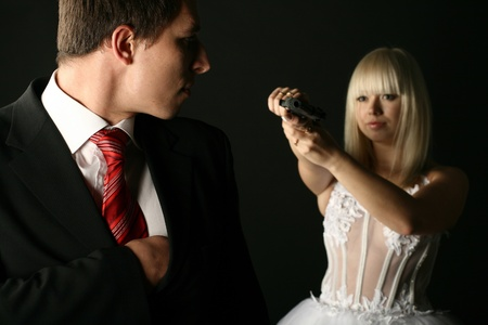 bride in white dress with pistol wants to kill her boy in black