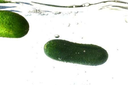 cucumber splash isolated on white background photo