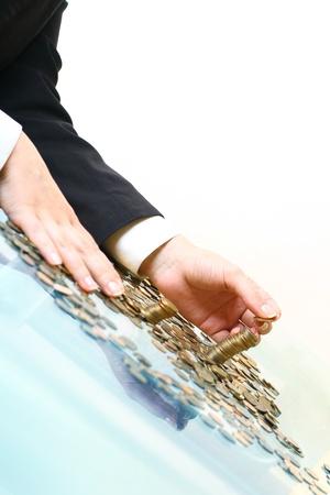 dare soldi: mano fanno mucchi monete su bianco