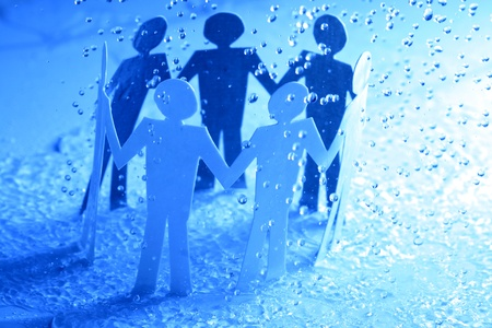 cooperative: paper team linked together under rain weather concept