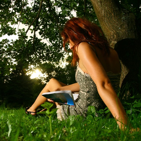 mujer leyendo libro: Hermosa niña de lectura bajo el árbol Foto de archivo