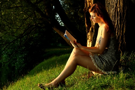 Beautiful girl reading under the tree photo