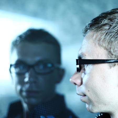 mirar espejo: el hombre y su reflejo en el vidrio Foto de archivo