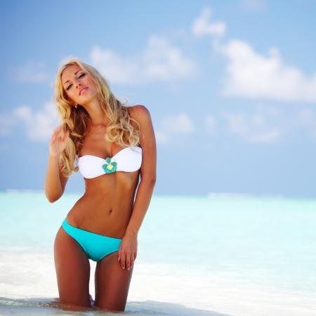 swimsuits: woman in bikini on sea beach Stock Photo